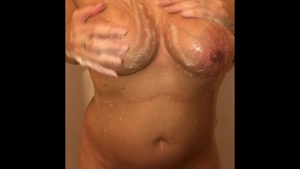 Busty MILF masturbating in the shower solo